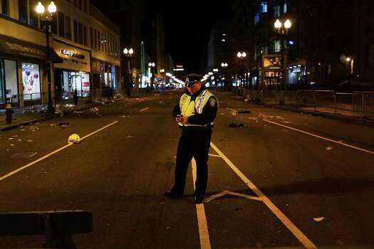BOSTON, MA - APRIL 16:  A Boston police officer stands near the scene of a twin bombing at the Boston Marathon, on April 16, 2013 in Boston, Massachusetts. Three people are confirmed dead and at least 141 injured after the explosions went off near the finish line of the marathon yesterday. The bombings at the 116-year-old Boston race, resulted in heightened security across the nation with cancellations of many professional sporting events as authorities search for a motive to the violence. Photo: Spencer Platt, Getty Images / 2013 Getty Images