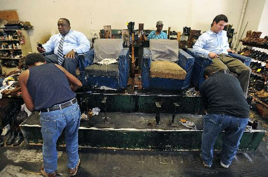 Roney Phillips, left, and Glenn Segura shine shoes at Mirror Shine & Shoe Repair. Guiseppe Barranco/cat5