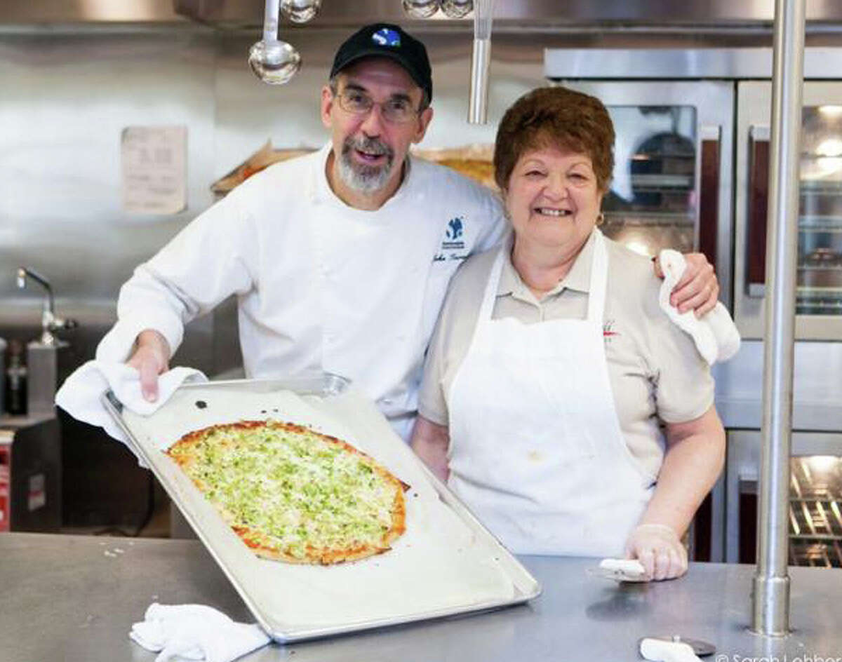 """No more """"mock pizza"""" in the new menus being developed at Fairfield public schools under guidance of consultant John Turenne, the founder and president of Sustainable Food Systems, shown with Pat Brienza, the manager/cook at McKinley School. The pizza served at the school is now the real thing with a whole-grain crust and topped with a five-vegetable tomato sauce."""