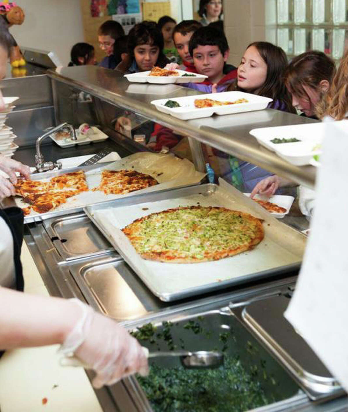 Students line up for lunch at McKinley School, one of two schools where new, healthier menus are being prepared and served under a pilot program this year.