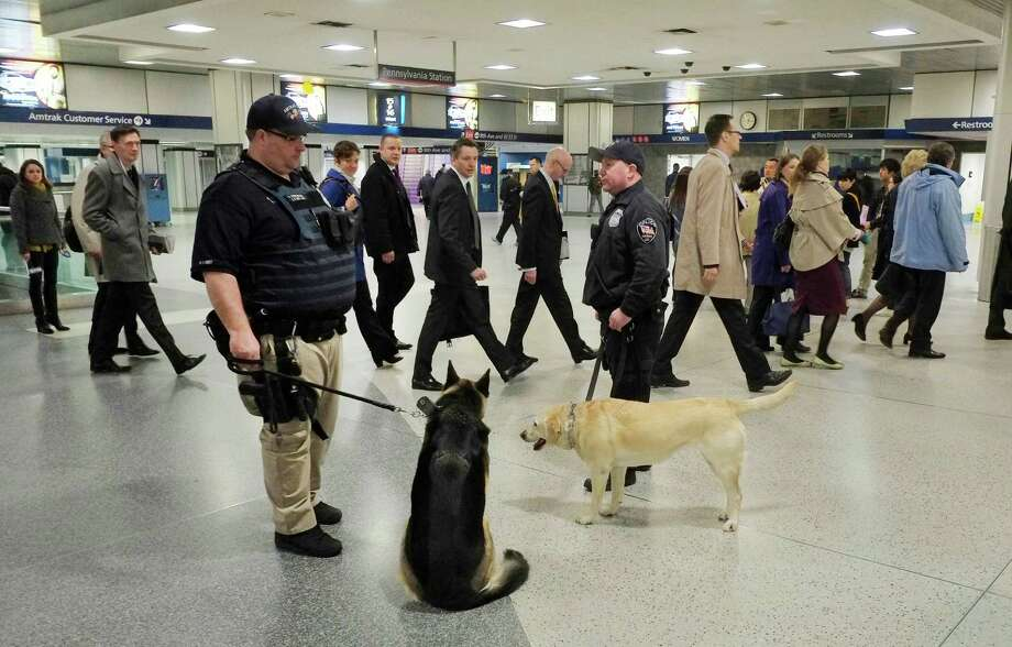 Amtrak police officers and their dogs watch as commuters walk through Penn Station, Tuesday, April 16, 2013 in New York. The deadly explosions at the Boston Marathon on Monday reverberated on both sides of the Atlantic as cities from Los Angeles to London saw a surge in security. Photo: Mark Lennihan, AP / AP