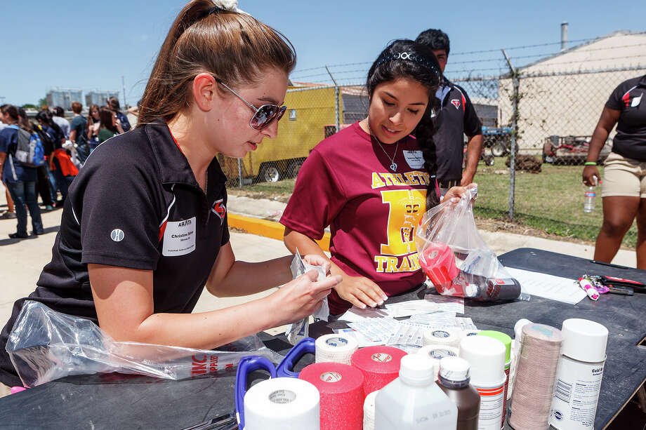 Stevens' Christine Behne (left) races against Harlandale's Sabrina Aguilar to assemble medical supplies in an obstacle course race during the 2013 Alamo Area Athletic Trainers' Association's Student Trainer Workshop at the  Region 20 Education Service Center,1314 Hines Ave., on Friday.  Student Trainers (and Athletic Trainers) from all San Antonio and surrounding schools gathered to learn and compete at the event. Photo: MARVIN PFEIFFER, Marvin Pfeiffer / Northwest Weekly / Prime Time Newspapers 2013