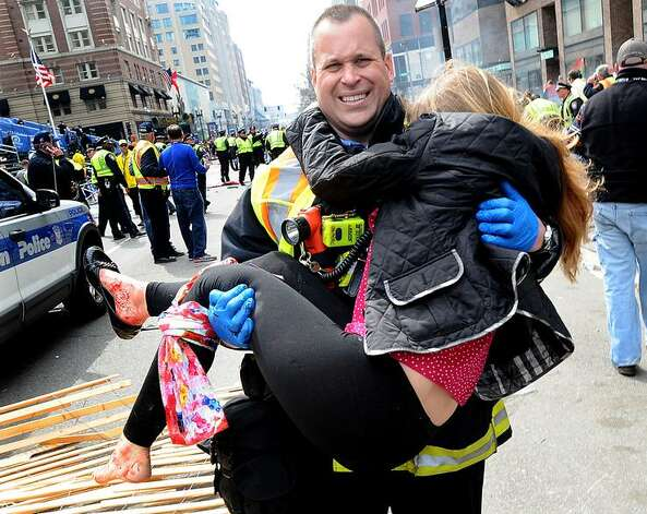 James Plourde, a Boston firefighter who graduated for Colonie High School in 1995, carries a victim away from the bombing scene in Boston on Monday, April 15, 2013. The photograph has gone viral, spreading rapidly on the internet. (Photo by Ken McGagh / MetroWest Daily News.)