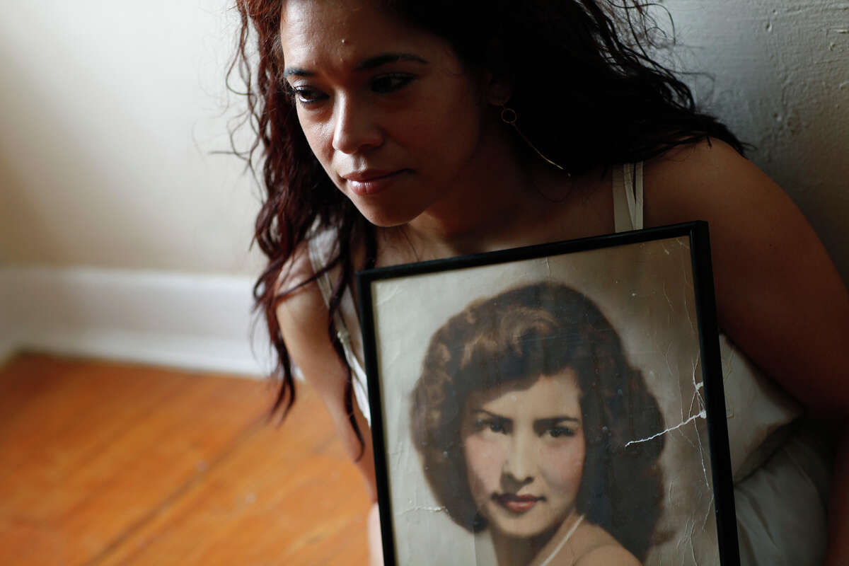 Cecilia Penix holds a photograph of her mother, Amelia Castillo, at Penix's home in San Antonio on Thursday, April 23, 2009. Cecilia was shot in the hand and her mother was killed by the sniper, Ira Attebury, during the 1979 Battle of Flowers Parade.
