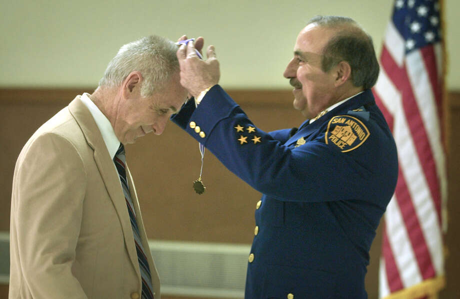 San Antonio Police Chief Albert Ortiz (right) places the Purple Heart Medal around the neck of Sgt. Louis Grassmuck for his outstanding police work during the 1979 Fiesta parade sniper incident, Tuesday, March 4, 2003. Photo: BOB OWEN, SAN ANTONIO EXPRESS-NEWS / SAN ANTONIO EXPRESS-NEWS