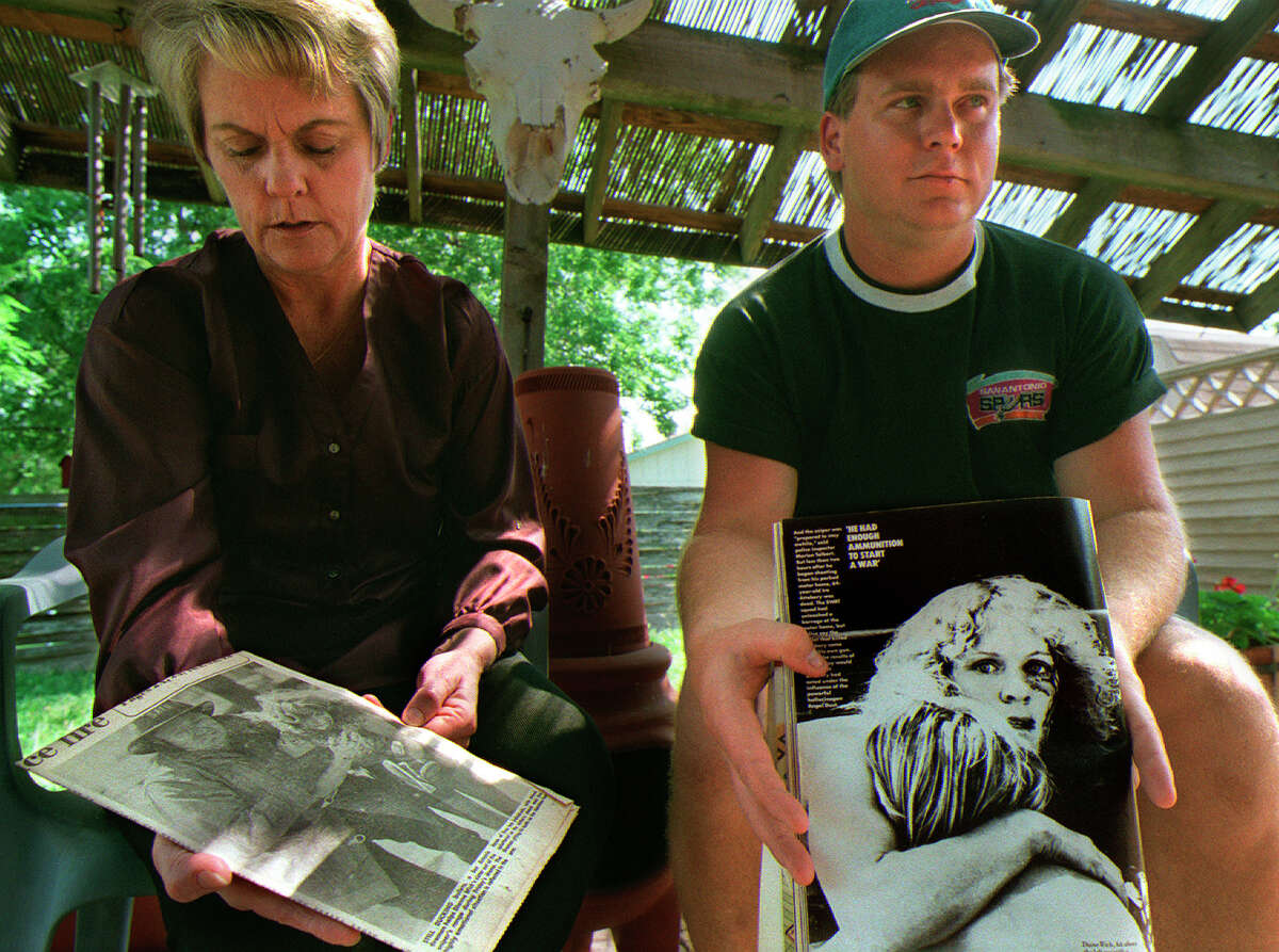 Kathi Sikes and her son T.J. Lapping hold clips of pictures taken of them during the sniper shooting at the Battle of Flowers Parade in 1979. The two were at Sikes' home Sunday, April 11, 1999.
