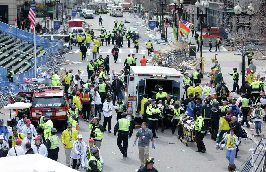 Medical workers aid injured people at the finish line of the 2013 Boston Marathon following an explosion in Boston, Monday, April 15, 2013. (AP Photo/Charles Krupa) Photo: Charles Krupa, Associated Press / AP