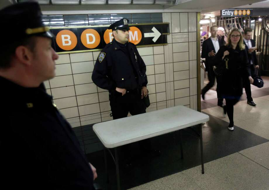 Police officers keep an eye on commuters in a subway station in New York, Tuesday, April 16, 2013. Police armed with rifles and extra patrol cars were stationed around the city Tuesday as New York remained in a heightened state of alert until more is known about the bombings at the Boston Marathon. Photo: Seth Wenig, AP / AP