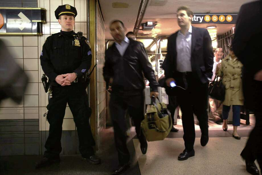 A Police officer  keep an eye on commuters in a subway station in New York, Tuesday, April 16, 2013. Police armed with rifles and extra patrol cars were stationed around the city Tuesday as New York remained in a heightened state of alert until more is known about the bombings at the Boston Marathon. Photo: Seth Wenig, AP / AP