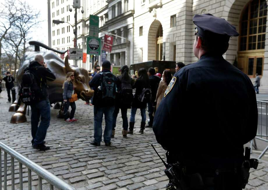 A New York City Police officer watches as people take pictures with the bull statue in the Financial District, Tuesday, April 16, 2013 in New York. Law enforcers say New York City remains in a heightened state of alert until more is known about the Boston explosions. More officers are working around New York, including counterterrorism units and beefed up patrols. Photo: Richard Drew, AP / AP