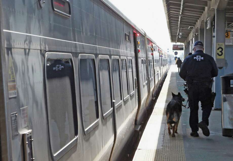 HICKSVILLE, NY - APRIL 15:  A police officer with his K-9 companion keeps guard as a Long Island Rail Road train from New York City arrives at the station on April 15, 2013 in Hicksville, New York. According to reports, at least two people were killed and 28 injured in two blasts near the finish of the Boston Marathon on Monday. Photo: Bruce Bennett, Getty Images / 2013 Getty Images