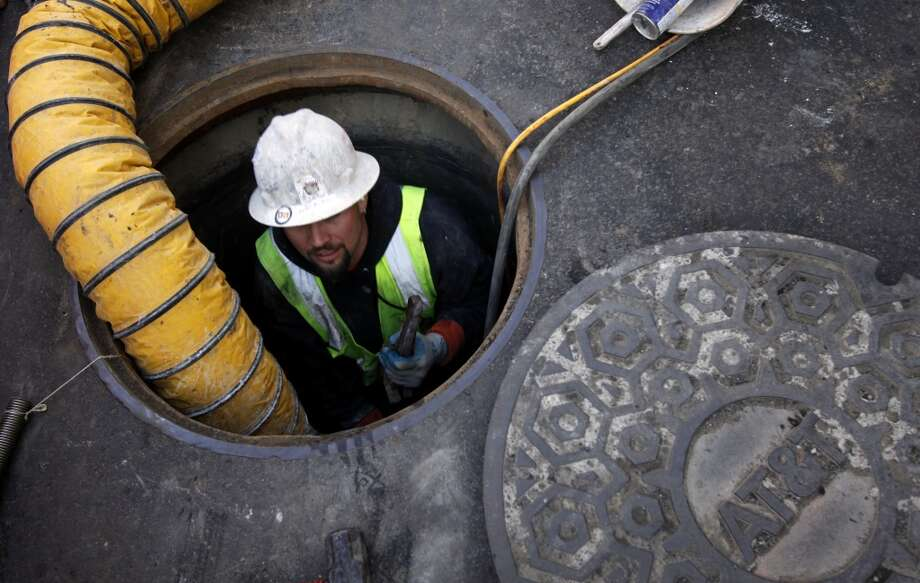Dino Asko emerges from a manhole where he was boring holes to reroute utilities under Geary St. for the Central Subway in San Francisco, Calif., Friday, February 17, 2012.