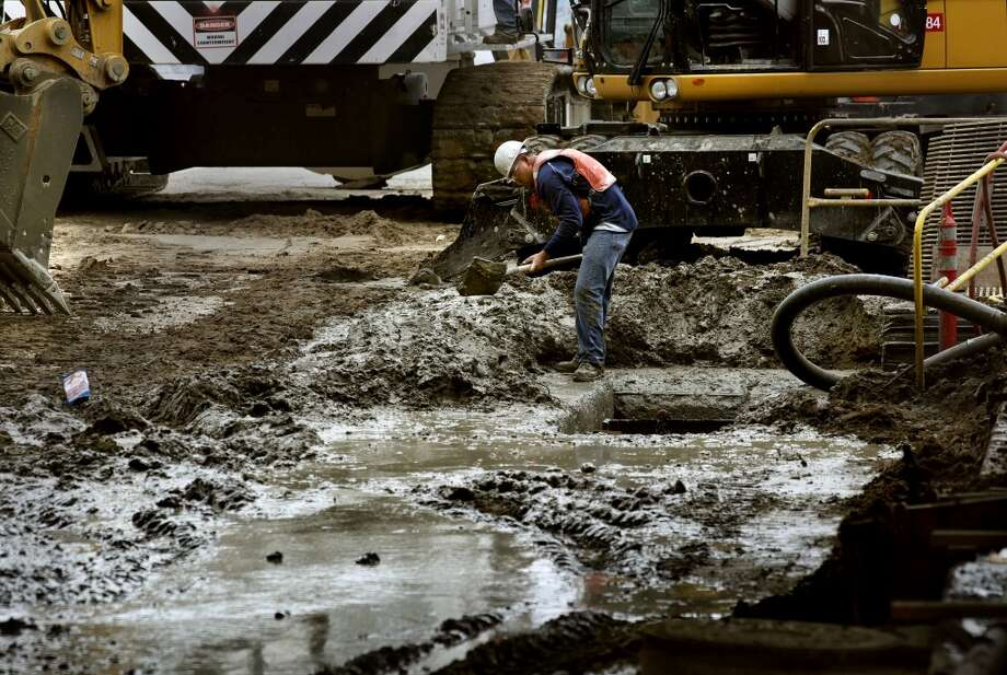 Francisco Esquivel shovels mud away from the construction of the slurry walls for the Central Subway project through downtown San Francisco, Calif. along Fourth Street, between Harrison and Bryant Streets, on Friday July 13, 2012.