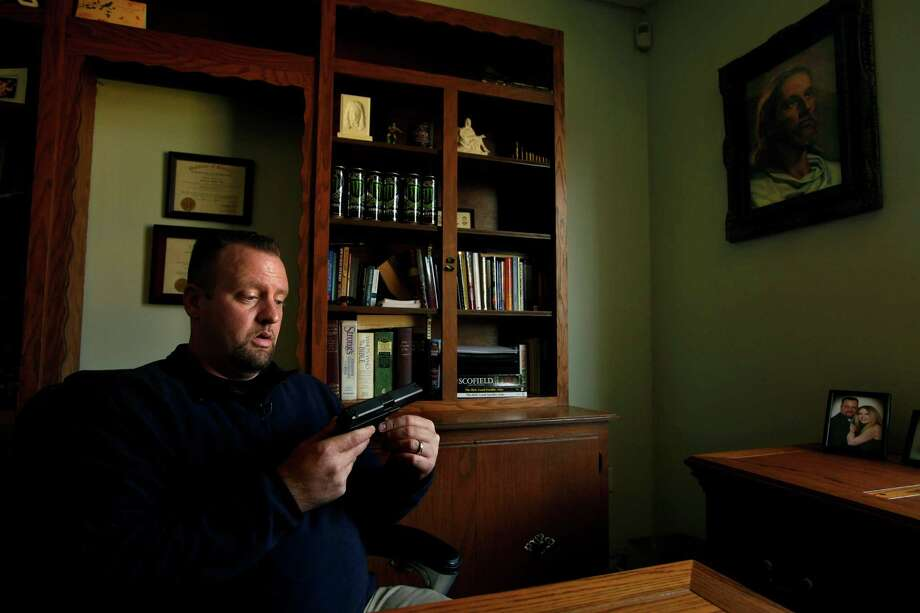 """People think I'm a gun nut and gun crazy, but I'm not. I don't want to hurt anybody. I believe the Bible teaches peace. But that doesn't mean I should let them hurt me,"" says Rev. James McAbee. McAbee, who gained local fame as the ""pistol-packing-pastor"" two years ago, after he foiled a burglary at his church, wears a gun at all times. He wear a shirt advertising his classes in his church office. (Carolyn Cole/Los Angeles Times/MCT) Photo: Carolyn Cole, MBR / Los Angeles Times"