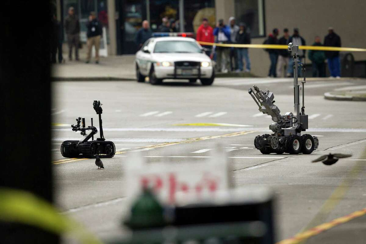 The Seattle Police Department's arson and bomb squad investigates and clears the site of a suspicious package with the help of robotic technology Tuesday, April 16, 2013, near 3rd Avenue and Yesler Way in Pioneer Square in Seattle. The package, a black backpack containing what was later discovered to be a hair dryer, was removed from the scene and traffic quickly resumed.