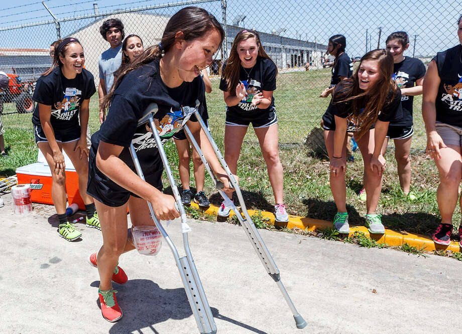 Reagan's Maddie McClain races on crutches after having her knee wrapped with ice as teammates cheer her on in an obstacle course race against MacArthur in the Alamo Area Athletic Trainers' Association's student trainer workshop on Friday. Photo: Marvin Pfeiffer / North Central News
