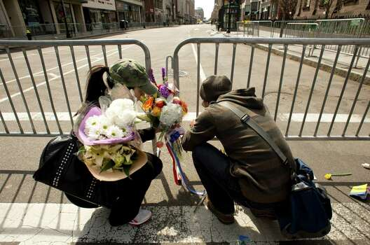 Two poeple lay flowers at a memorial site at Boylston and Arlington streets along the course of the Boston Marathon on April 16, 2013, a few blocks from where two explosions struck near the finish line of the Boston Marathon on April 15. The explosives used in the Boston Marathon bombings were likely homemade devices full of nails and metal fragments designed to cause widespread injury, according to initial reports. A day after an attack that left three dead and more than 170 wounded, the FBI and Boston police declined to reveal details of their probe, or whether they suspected the assault was linked to foreign or domestic extremists. Photo: DON EMMERT, Getty Images / 2013 AFP