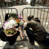 Two poeple lay flowers at a memorial site at Boylston and Arlington streets along the course of the Boston Marathon on April 16, 2013, a few blocks from where two explosions struck near the finish line of the Boston Marathon on April 15. The explosives used in the Boston Marathon bombings were likely homemade devices full of nails and metal fragments designed to cause widespread injury, according to initial reports. A day after an attack that left three dead and more than 170 wounded, the FBI and Boston police declined to reveal details of their probe, or whether they suspected the assault was linked to foreign or domestic extremists.