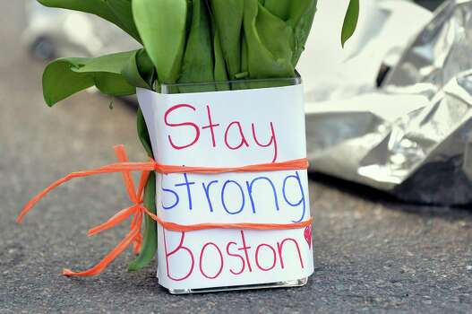Flowers and a message are left on Newbury Street April 16, 2013 in Boston, Massachusetts, a few blocks from where two explosions struck near the finish line of the Boston Marathon on Monday. Three people, including a child, were killed and more than 170 were injured in the explosions that occurred a few seconds apart near the finish line of the 117th rendition of the world's oldest international marathon Photo: Getty Images