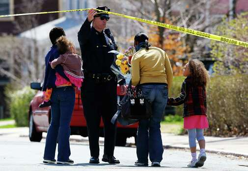 A Boston Police officer lifts the tape for a family to leave flowers in front of the home of the Richard family whose eight-year-old son, Martin, was killed by an explosion near the finish line of the Boston Marathon, on April 16, 2013 in Boston, Massachusetts. The twin bombings resulted in the deaths of three people and hospitalized at least 128. The bombings at the 116-year-old Boston race resulted in heightened security across the nation with cancellations of many professional sporting events as authorities search for a motive to the violence. Photo: Jared Wickerham, Getty Images / 2013 Getty Images