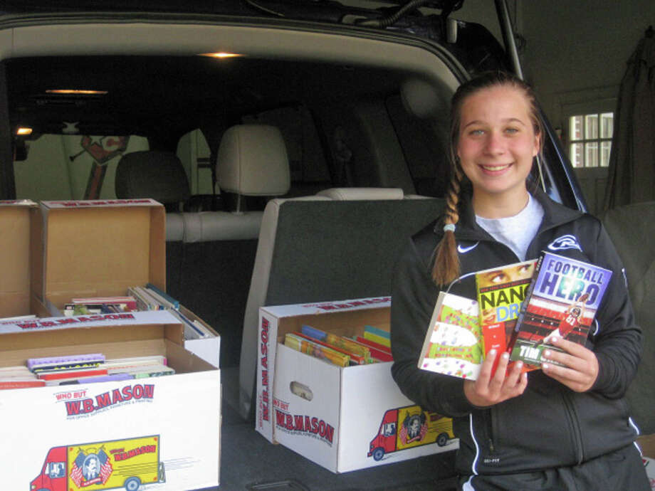 Alyssa Valente, a sophomore at New Canaan High School, collected more than 300 gently used books to donate to an East Rockaway school library. Photo: Contributed Photo