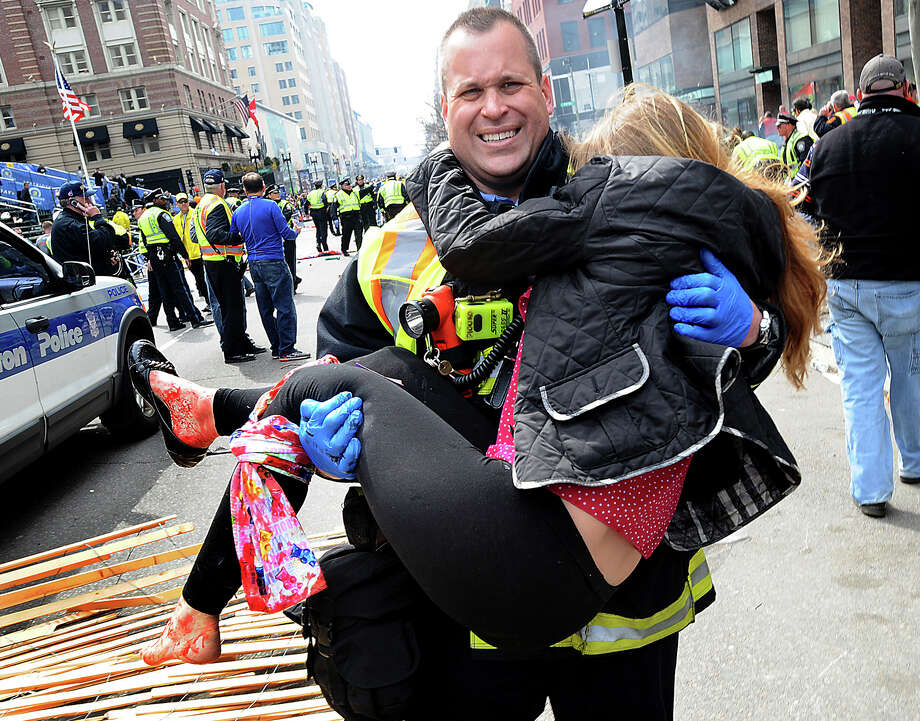 In this Monday, April 15, 2013 photo, Boston Firefighter James Plourde carries an injured girl away from the scene after a bombing near the finish line of the Boston Marathon in Boston. The FBI's investigation into the bombings at the Boston Marathon was in full swing Tuesday, with authorities serving a warrant on a suburban Boston home and appealing for any private video, audio and still images of the blasts that killed at least three and wounded more than 170. (AP Photo/MetroWest Daily News, Ken McGagh)  MANDATORY CREDIT Photo: Ken McGagh / MetroWest Daily News