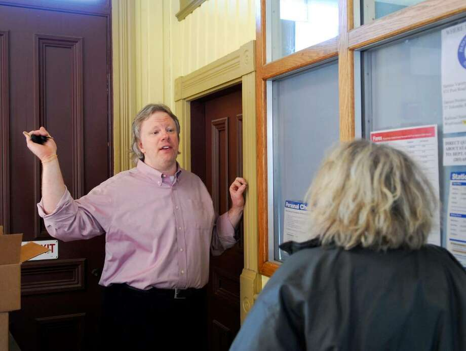 Metro-North ticket agent in the Darien station, Jeff Fleming, left, speaks with a customer about the train schedule inside the Darien Station on Wednesday Jan. 6th, 2009.  Fleming will move to another job within the MetroNorth system as the Darien ticket agent job is being eliminated. Photo: Bob Luckey / Stamford Advocate