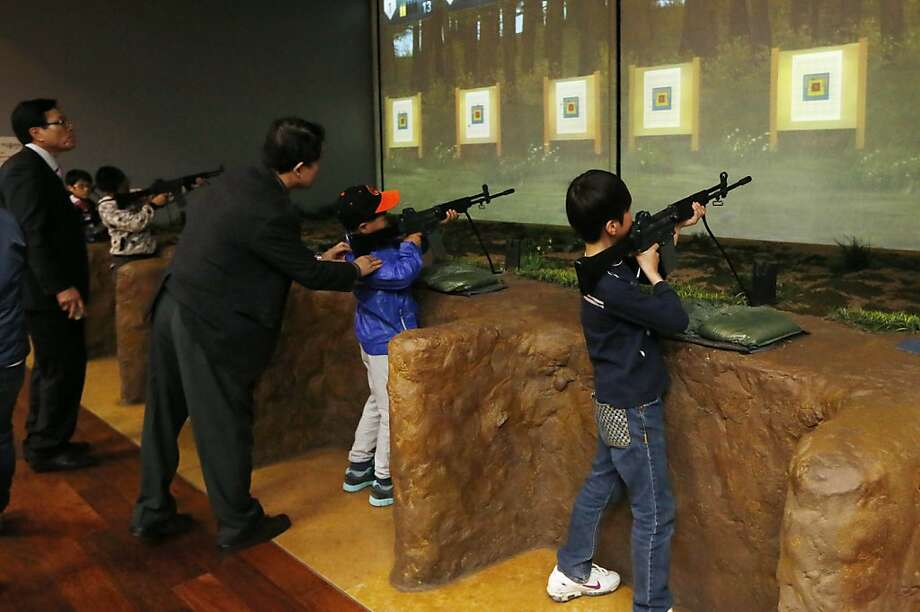 "Pupils shoot targets from a ""trench"" at the Korea War Memorial Museum in Seoul, South Korea. Photo: Kin Cheung, Associated Press"
