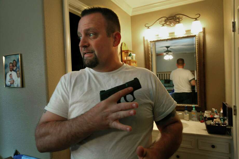 FILE - Rev. James McAbee, left, and his wife Misty keep their guns in a nearly 5-foot-tall blue Field & Stream gun safe in the bedroom of his ranch house when they aren't wearing them. McAbee, a pastor at the Lighthouse Worship Center in Beaumont, Texas also teaches concealed handgun classes. (Carolyn Cole/Los Angeles Times/MCT) Photo: Carolyn Cole, MBR / Los Angeles Times