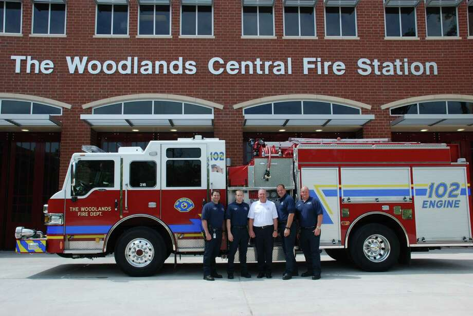 The Woodlands Central Fire Station will open April 23 with firefighters uncoupling hoses rather than cutting a ribbon. At left are firefighter Richard Reeg, firefighter and paramedic Tyler Knutson, Chief Alan Benson, Lt. Jason Hearnsberger and firefighter and paramedic Adrian Dinges. The firefighters also will push the fire engine into the bay, another tradition when opening a station. Photo: Lindsay Peyton