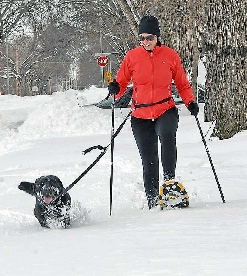 High-stepping: Katie Kost cruises on snowshoes through deep snow in Bismarck, N.D.'s historic Cathedral District, while Jake gets by on just paw pads. Photo: Tom Stromme, Associated Press