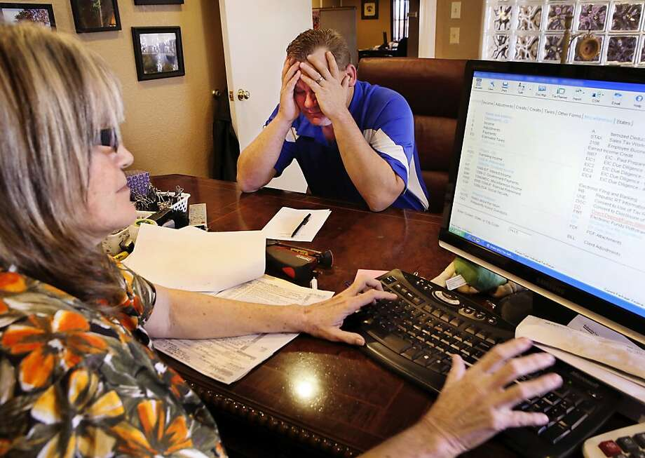 Unhappy returns:In Del City, Okla., filing procrastinator Colin Turn learns from tax service owner Vickie Eubanks that he and his wife will owe additional taxes this year. Photo: Jim Beckel, Associated Press