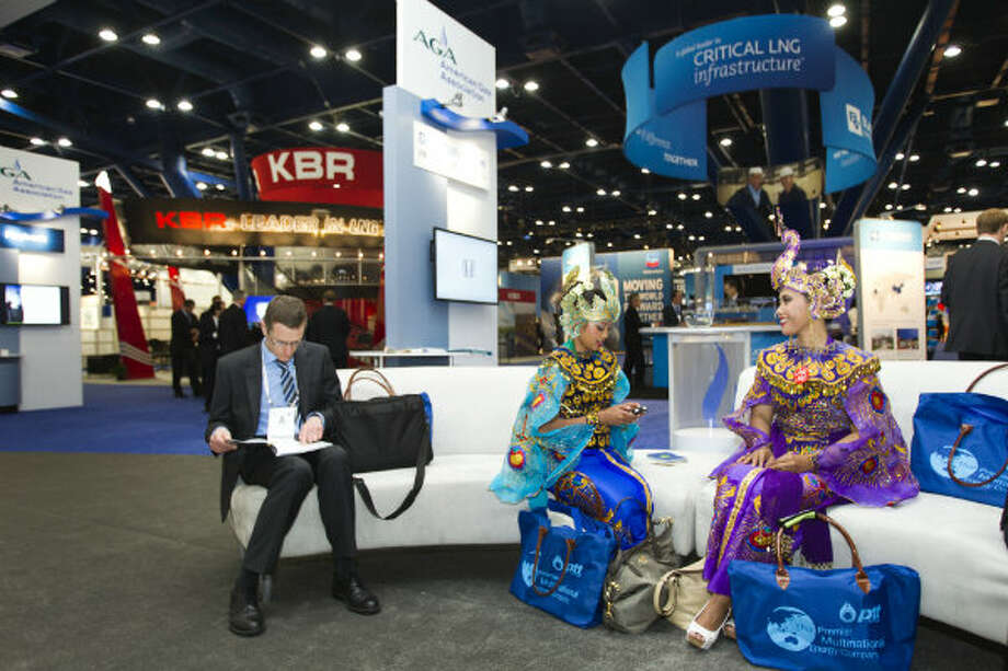 Jose Simon, of Spain, left, takes a seat next to Andri Ani, center, and Wiyah Derma Ida, who are working in the Pertamina booth from Indonesia, during the 17th International Conference & Exhibition on Liquefied Natural Gas at the George R. Brown Convention Center Tuesday, April 16, 2013, in Houston. Photo: Brett Coomer, Houston Chronicle