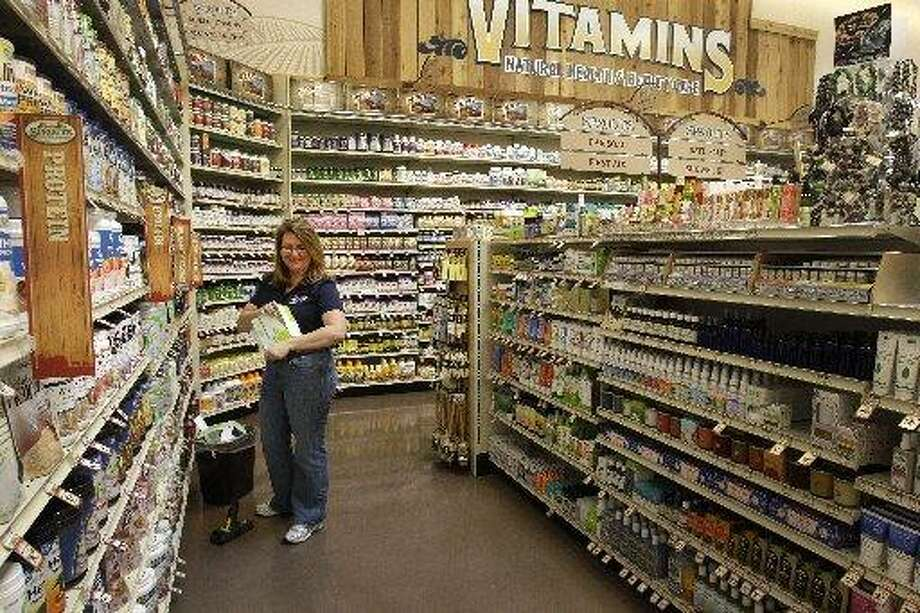 Ericka Barnes, a regional support trainer, works on displaying items in the vitamin and health and beauty department at the new Sprouts Farmers Market, 22506 Tomball Parkway. Photo: Melissa Phillip, Houston Chronicle