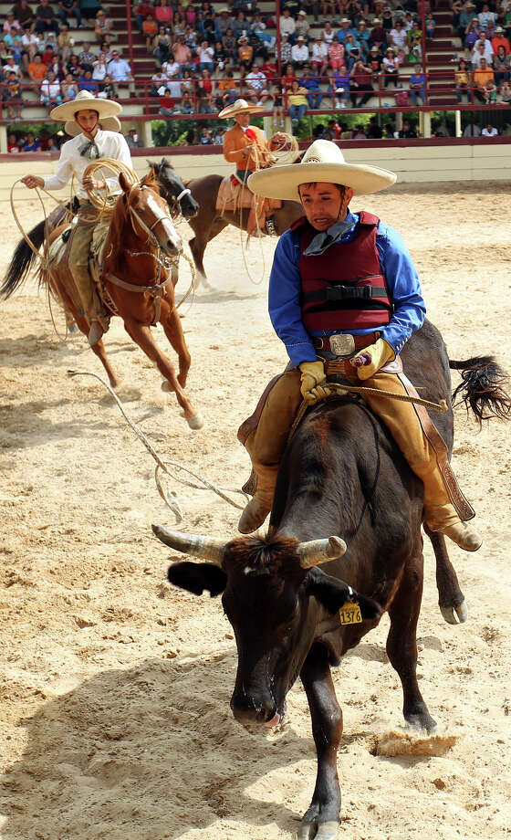 Bull rider Augustine Cervantes nears the end of his ride during the Fiesta Charreada at the San Antonio Charro Ranch, Sunday, April 17, 2011. (Jennifer Whitney/ Special to the San Antonio Express-News) Photo: Jennifer Whitney, Special To The Express-News / SAN ANTONIO EXPRESS-NEWS