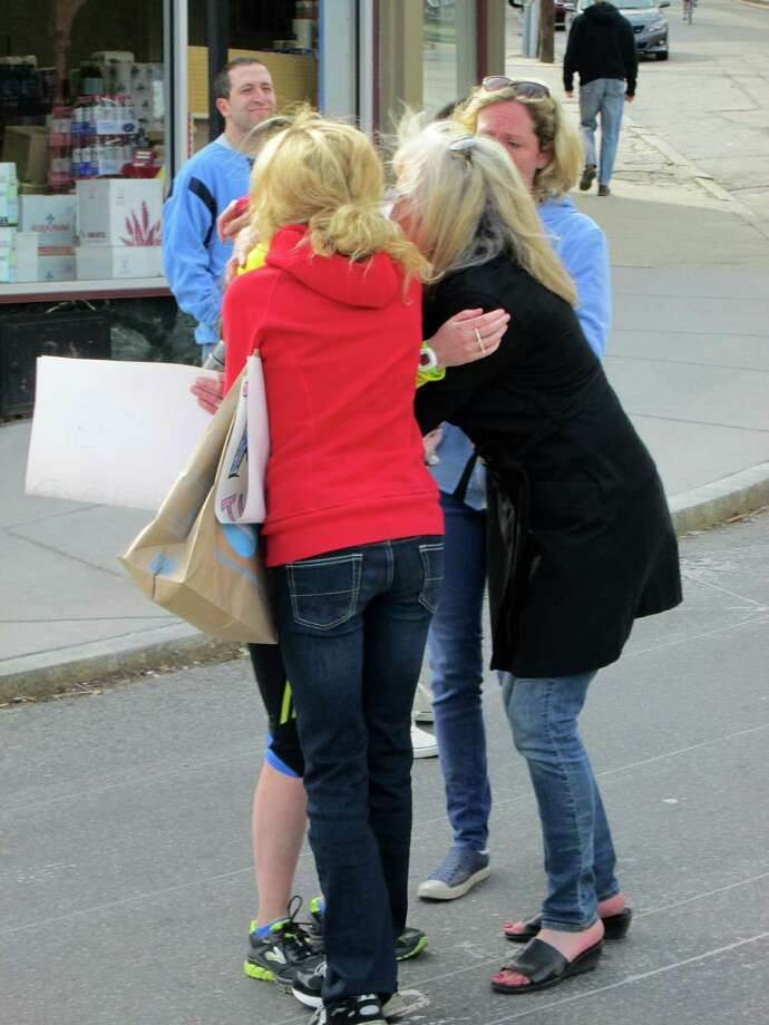 Sharon Daly hugs her daughter Julia as her other daughters, Tara and Kate wait their turn. Michael Daly and his family were in Boston to cheer on his daughter Julia as she ran in the Boston Marathon on Monday April 15, 2013. Photo: Michael Daly / Connecticut Post