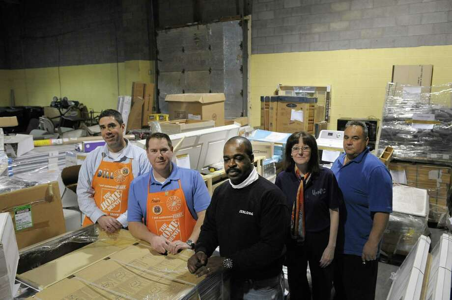 From left to right, William Burdick, district operation manager for Home Depot, Scott Raymond, Home Depot Latham Farms store manager, Lorenzo Hodges, director, Jezreel International, Chris Schultz, with Upstate New York Cares and Thomas Cunsolo, on the board of directors of the Staten Island Community and Interfaith Long Term Disaster Recovery Organization, all pose for a photograph near just some of the home and building items that are heading to Staten Island, on Monday, April 15, 2013 at Jezreel International in Colonie, NY.  The Capital area Home Depot stores are donating $45,000 dollars worth of supplies a month for the term of the project.  Cunsolo, who lives in Long Island, lost his home and his cars in the storm.   (Paul Buckowski / Times Union) Photo: Paul Buckowski