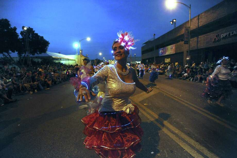 Terry Guillen of Charangas de San Antonio dances in the 2012 Fiesta Flambeau Parade, touted as the largest illuminated parade in the United States. Photo: Express-News File Photo