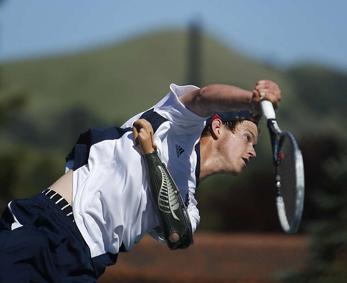 Alex Hunt watches his serve to his doubles opponent on Wednesday, April 10, 2013. Hunt is a freshman tennis player from New Zealand at St. Mary's College in Moraga, Calif. But that's not what makes him standout, he's playing Div. I tennis with a prosthetic left arm.