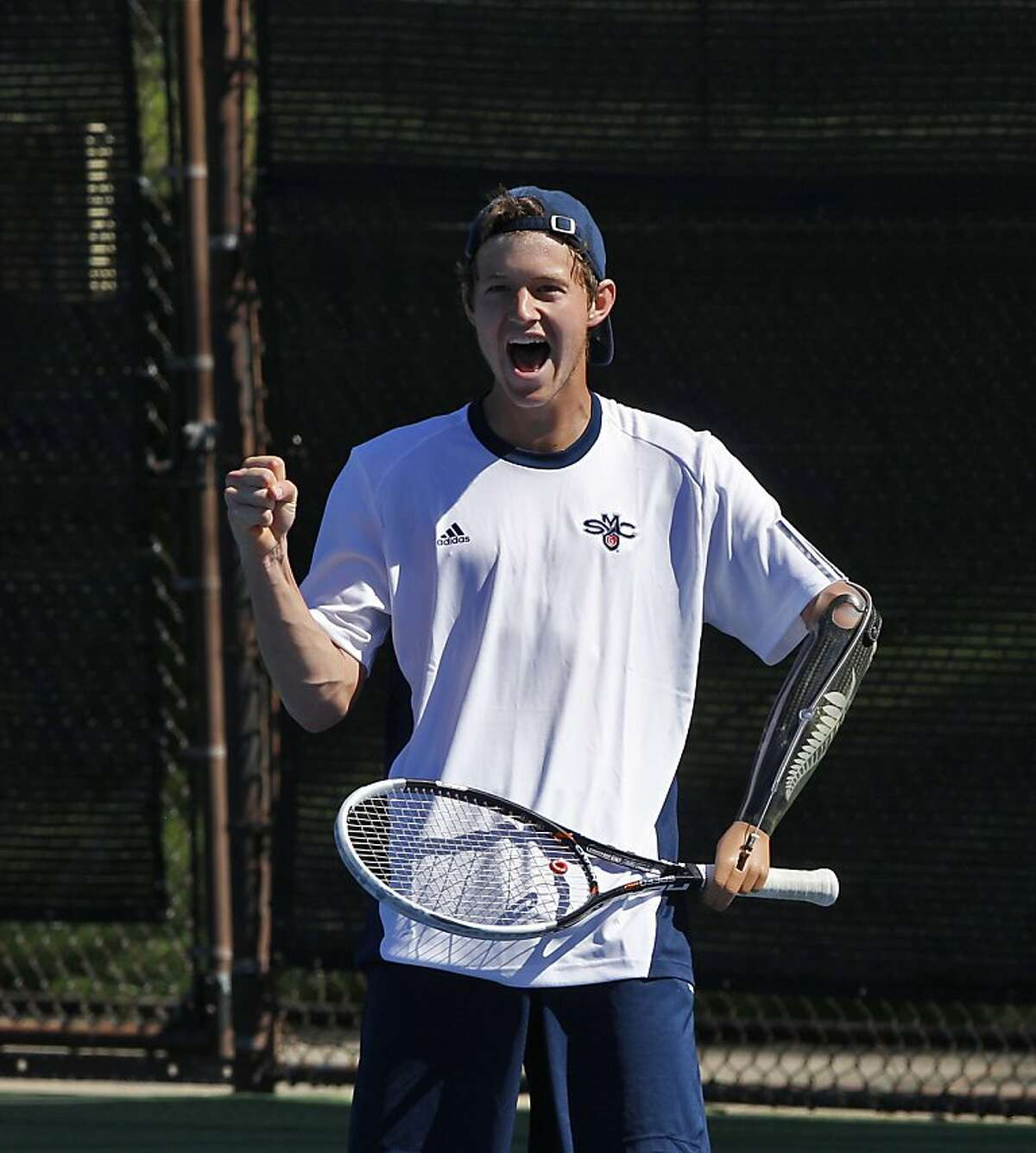 Alex Hunt celebrates a point against his doubles opponent on Wednesday, April 10, 2013. Hunt is a freshman tennis player from New Zealand at St. Mary's College in Moraga, Calif. But that's not what makes him standout, he's playing Div. I tennis with a prosthetic left arm.