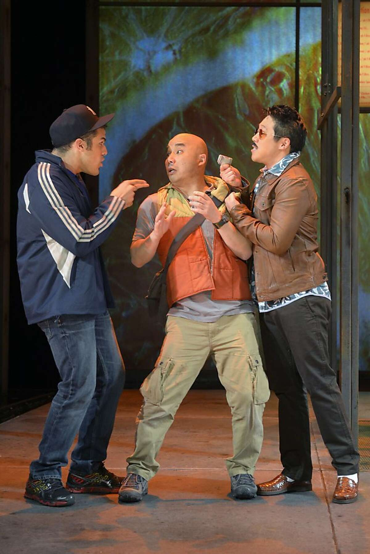 """Guang (Julius Ahn, center) gets waylaid by Marco (Joel Perez, left) and Snakehead (Raymond J. Lee) in ACT's """"Stuck Elevator"""" NOTE: Guang takes umlaut over the a"""
