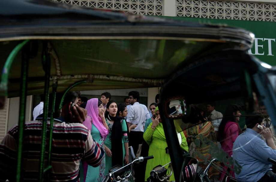 People evacuate buildings and gather on road as tremor of an earthquake was felt in Karachi, Pakistan, Tuesday, April 16, 2013. A major earthquake described as the strongest to hit Iran in more than half a century flatted homes and offices Tuesday near Iran's border with Pakistan, killing at least tens of people in the sparsely populated region and swaying buildings as far away as New Delhi and the skyscrapers in Dubai and Bahrain. (AP Photo/Shakil Adil) Photo: Shakil Adil