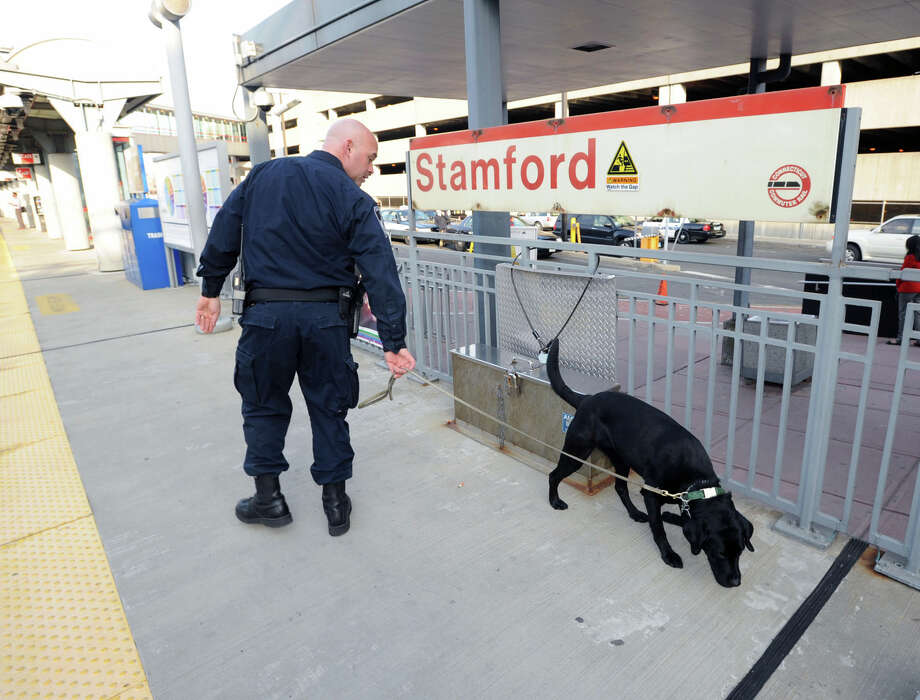 Stamford Police Officer Erin Trew and his black Labrador retriever, Riley, patrol the Stamford Train Station, Tuesday night, April 16, 2013. The Boston Marathon bombing has put the nation's police forces on high alert. Photo: Bob Luckey / Greenwich Time