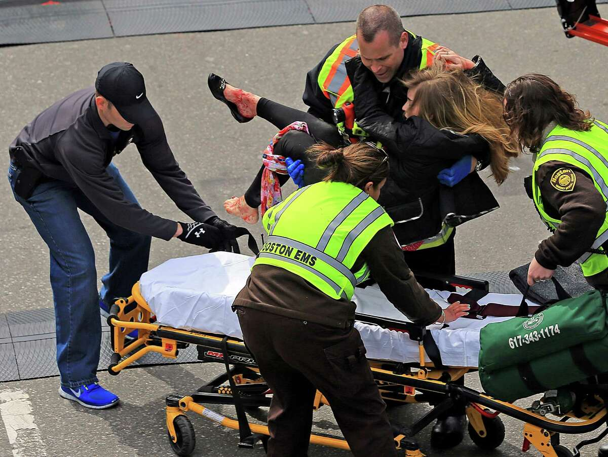 Rescue workers aid Victoria McGrath, a Northeastern University student from Weston , Conn. after she was injured in the explosions near the finish line at the Boston Marathon in Boston, Mass. on Monday, April 15, 2013.