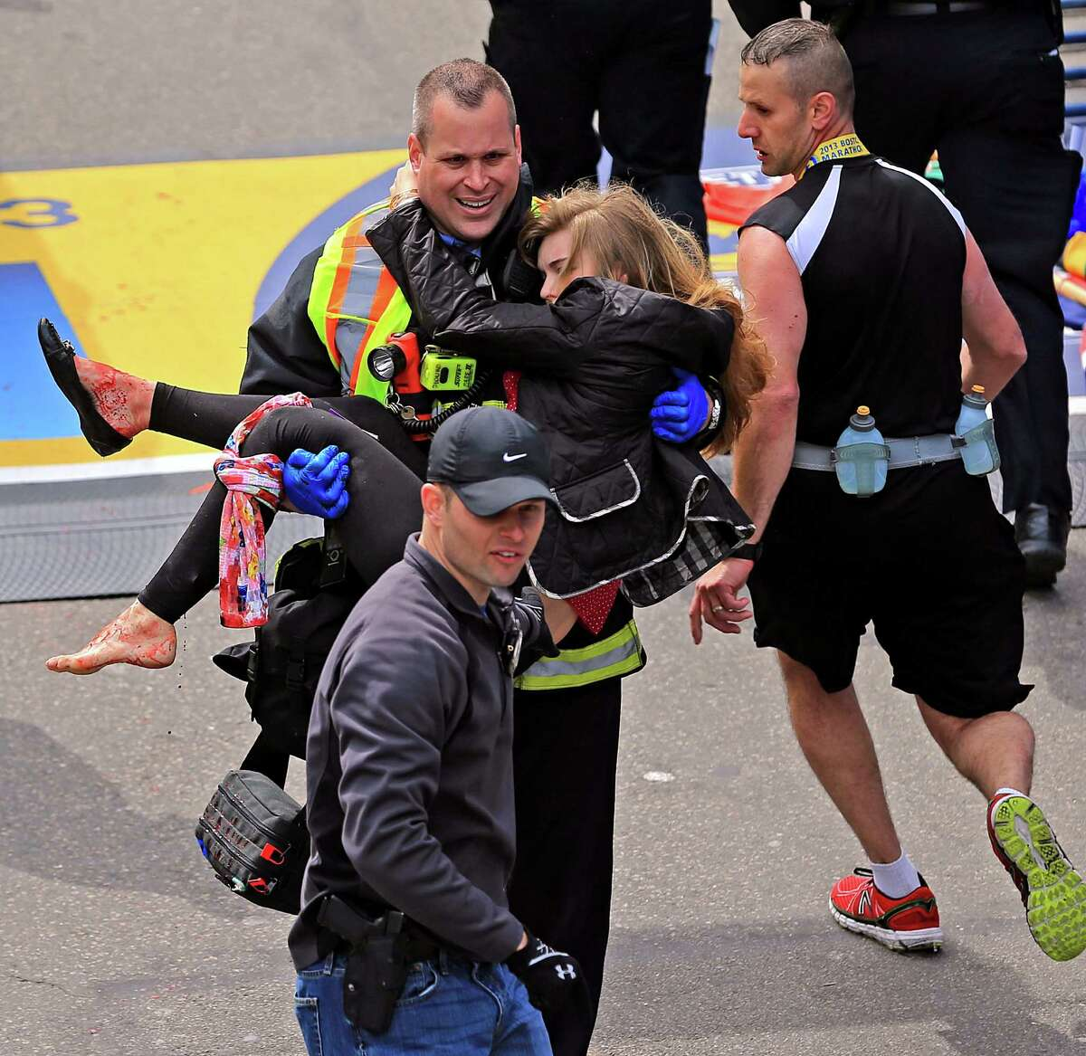 Emergency personnel aid Victoria McGrath, a Northeastern University student from Weston , Conn. after she was injured in the explosions near the finish line at the Boston Marathon in Boston, Mass. on Monday, April 15, 2013.