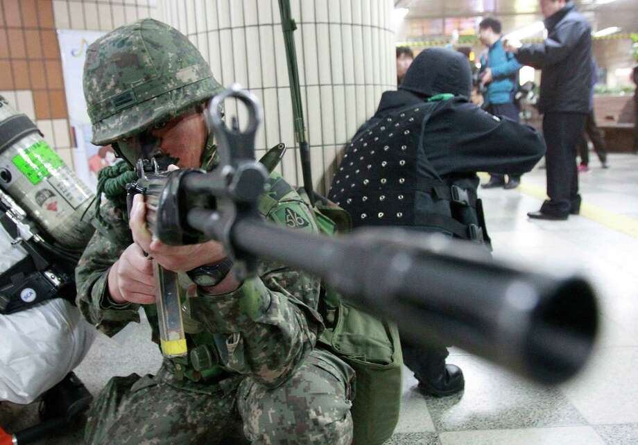 FILE - In this Monday, April 15, 2013 file photo, a South Korean army soldier aims his machine gun during an anti-terrorism drill against possible terrorists' attacks at a subway station in Seoul, South Korea. In his 16 months on the job, North Korean leader Kim Jong Un's government has raised fears with unusually aggressive threats against Seoul and Washington, and it's not clear whether he will be able to pull back, a feat perfected by his late father, considered a master at brinkmanship. The mystery surrounding Kim's intentions has some outsiders predicting nightmare scenarios. (AP Photo/Ahn Young-joon, File) Photo: Ahn Young-joon