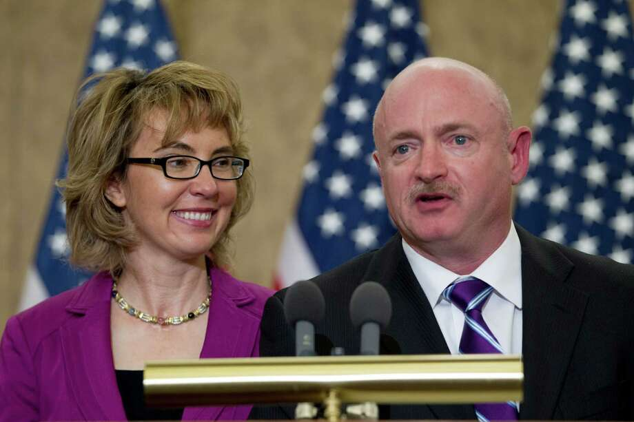 "Former Arizona Rep. Gabrielle Giffords listens as her husband, retired astronaut Mark Kelly speaks on Capitol Hill, in Washington, Tuesday,  April 16, 2013, during a ceremony to honor Gabriel ""Gabe"" Zimmerman.  Zimmerman was Giffords' outreach director until he was killed in the January 2011 shooting rampage in Tucson where Giffords was wounded.  (AP Photo/Jose Luis Magana) Photo: Jose Luis Magana"