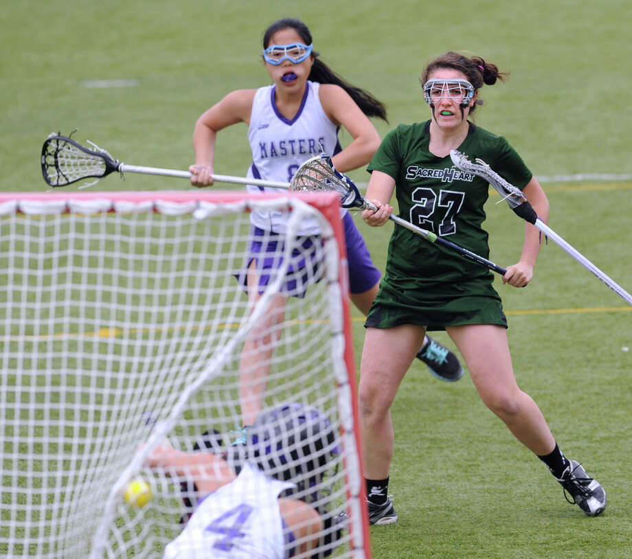 At right, Kate Larkin # 27 of Convnet of the Sacred Heart scores a first-half goal past Masters goal-keeper Casey Chon # 4 during the girls high school lacrosse match bewteen Convent of the Sacred Heart and Masters at Convent in Greenwich, Tuesday, April 16, 2013. Convent won the match 11-0. Photo: Bob Luckey / Greenwich Time