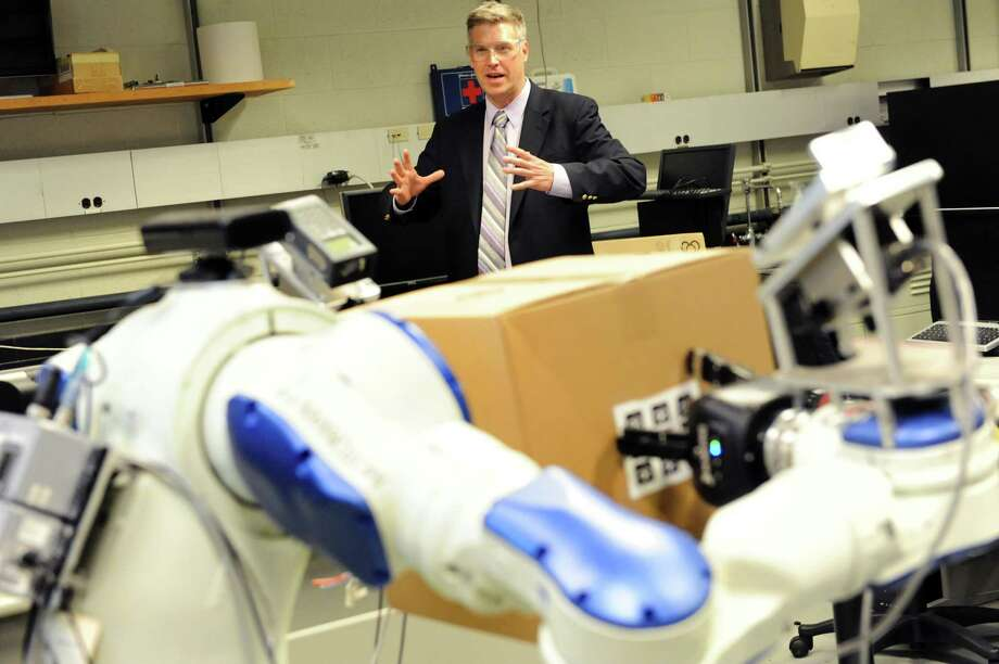 Patrick D. Gallagher, U.S. Under Secretary of Commerce for Standards and Technology, uses arm movements to direct a robot, in the foreground, during a tour on Tuesday, April 16, 2013, at Rensselaer Polytechnic Institute in Troy, N.Y. (Cindy Schultz / Times Union) Photo: Cindy Schultz / 10021987A