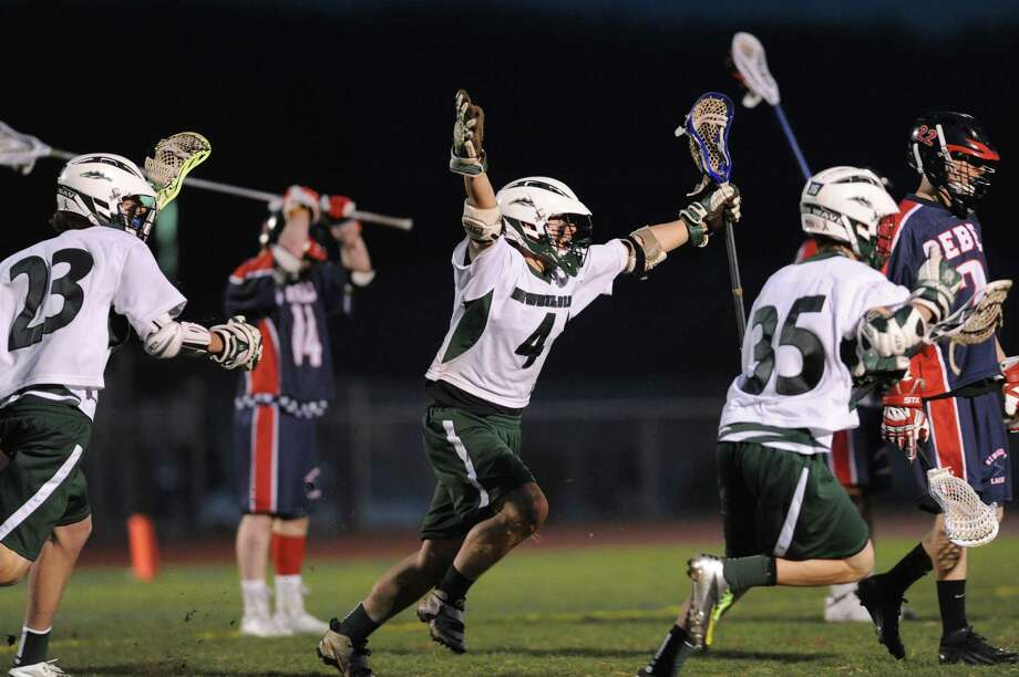 New Milford's Chris Reilly (4) celebrates with teammates Andre Beaudoin (23) and Justin Lourenco (35) after scoring the game-winning goal in New Milford's 8-7 overtime win against New Fairfield at New Milford High School in New Milford, Conn. on Tuesday, April 16, 2013. Photo: Tyler Sizemore / The News-Times